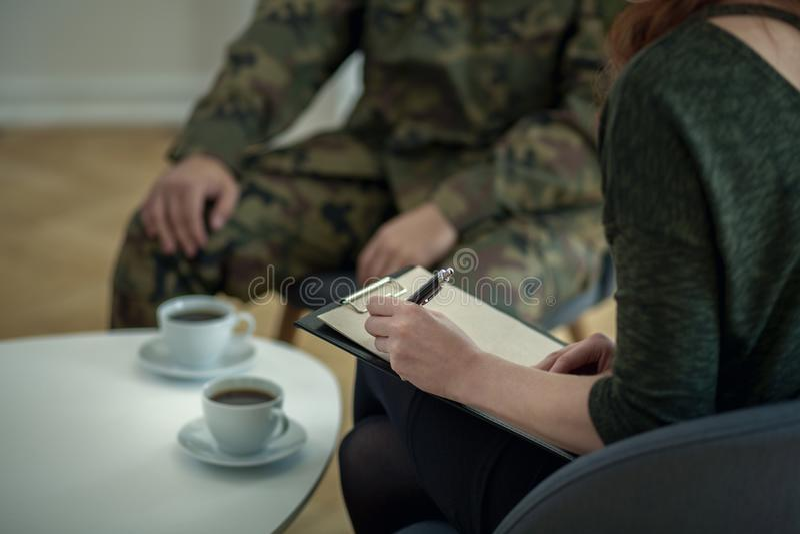 Primo piano dello psicologo che annota le note mentre parlando con suo paziente dall'esercito immagini stock