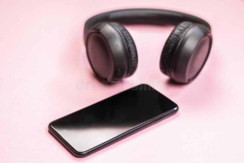 Primo piano dello Smart Phone con le cuffie su un fondo rosa immagine stock libera da diritti