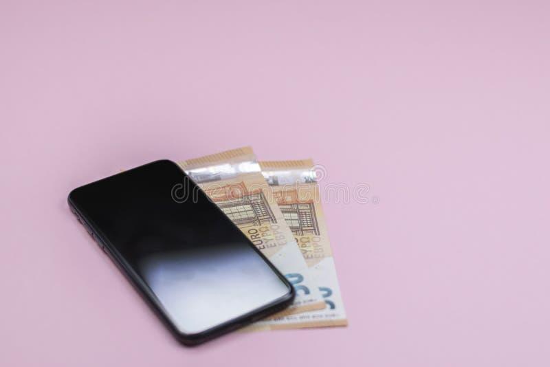 Primo piano dello Smart Phone con soldi su un fondo rosa fotografia stock libera da diritti