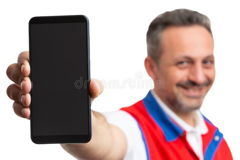 Primo piano dello smartphone tenuto dall'impiegato del supermercato immagini stock