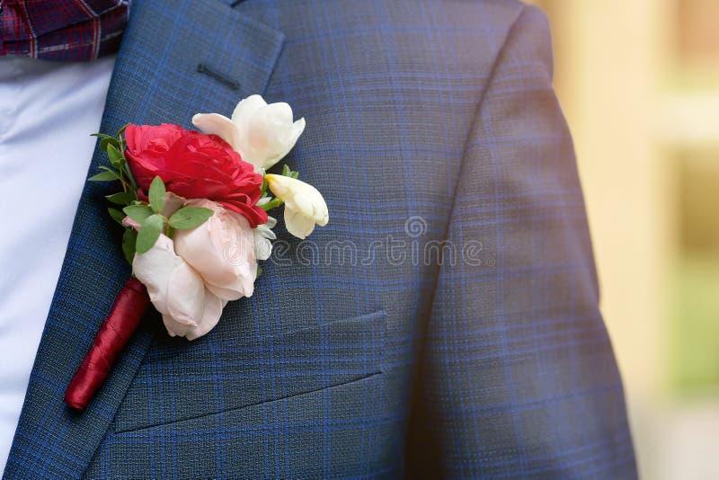 primo piano dello sposo di boutonniere su un fondo blu fotografia stock