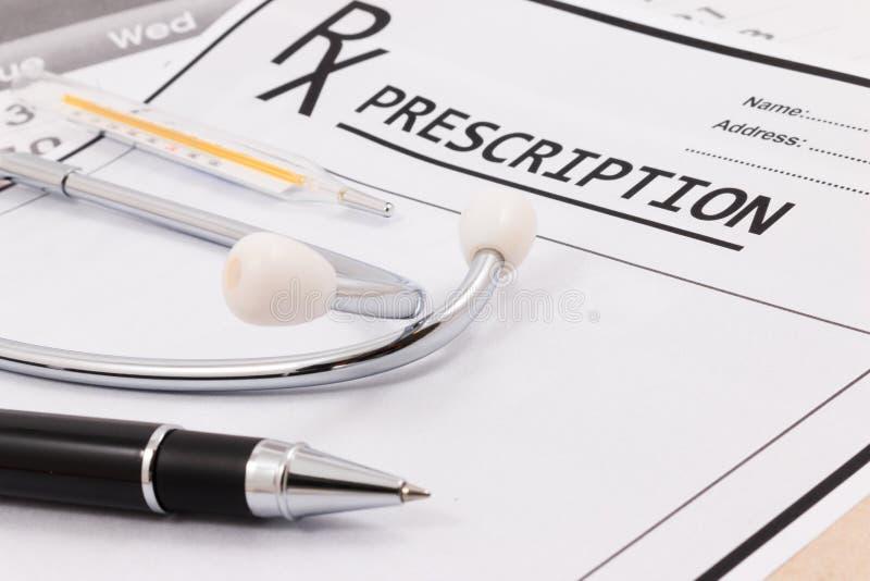 Primo piano dello stetoscopio, del termometro e della penna rossi su una prescrizione del rx immagine stock