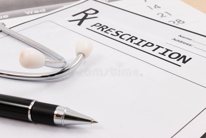 Primo piano dello stetoscopio e della penna rossi su una prescrizione del rx fotografia stock