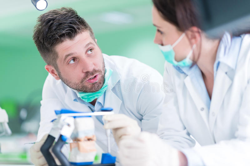 Primo piano dello studente di odontoiatria che pratica su un manichino medico immagine stock libera da diritti