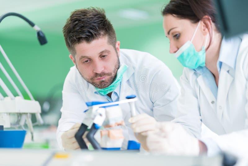 Primo piano dello studente di odontoiatria che pratica su un manichino medico immagini stock libere da diritti