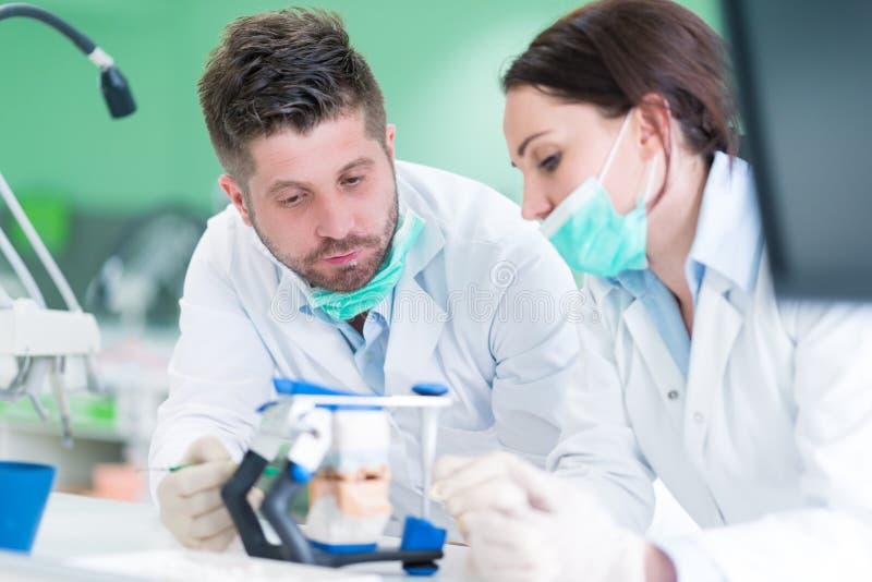 Primo piano dello studente di odontoiatria che pratica su un manichino medico fotografia stock