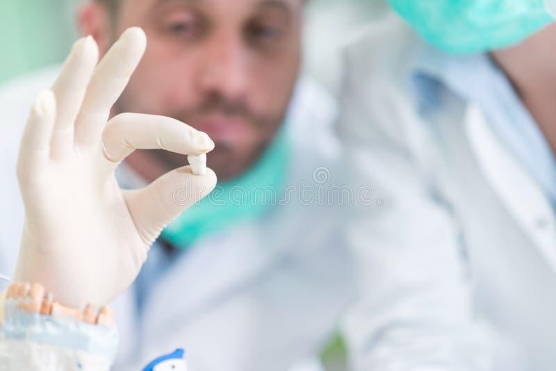 Primo piano dello studente di odontoiatria che pratica su un manichino medico immagine stock