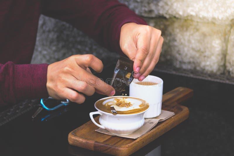 Primo piano dello zucchero di versamento della camicia dell'uomo in rosso mentre preparando la tazza di caffè calda fotografie stock libere da diritti