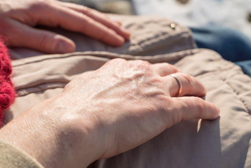 Primo piano dettagliato delle mani senior della donna sull'inverno fotografie stock