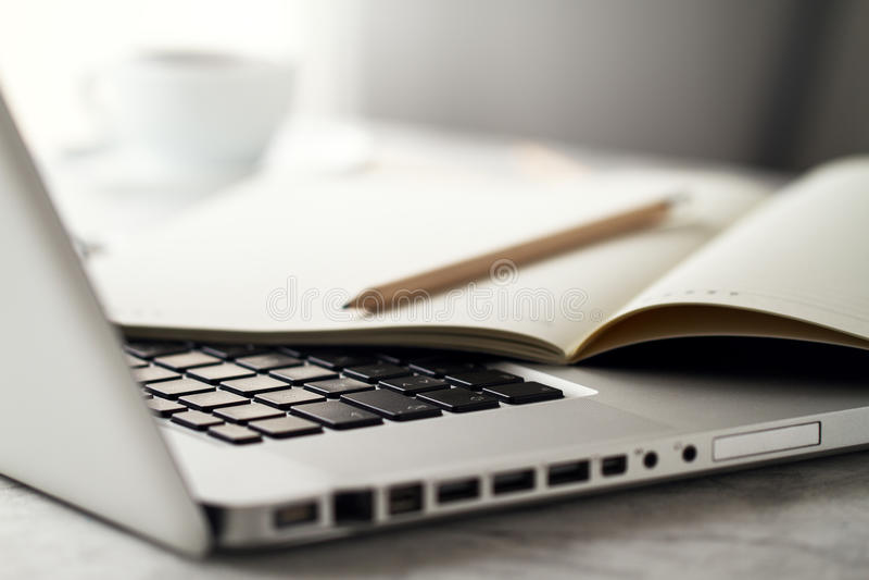 Primo piano di area di lavoro con il computer portatile creativo moderno, tazza di caffè fotografia stock libera da diritti