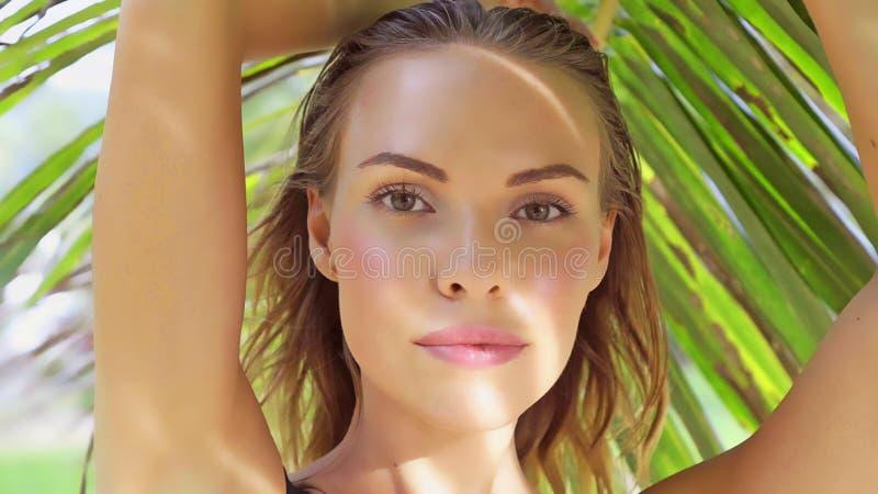Primo piano di bella donna di fascino che indossa swimwear nero che posa un bello giorno di estate fra le palme fotografia stock