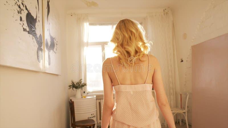 Primo piano di bella giovane donna bionda in biancheria beige di notte del cotone che cammina verso la finestra in suoi appartame fotografia stock libera da diritti