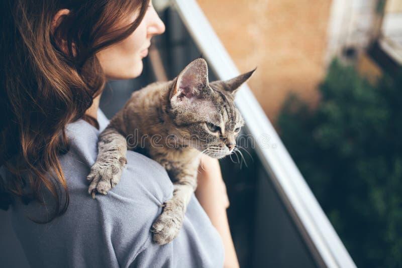 Primo piano di bella giovane donna che sta stando su un balcone con il suo gatto immagine stock libera da diritti