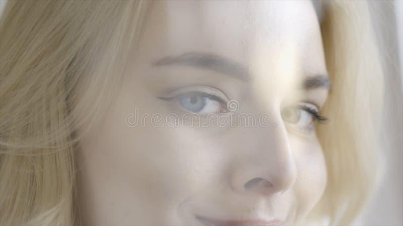 Primo piano di bella giovane donna favorita che guarda e che sorride azione Signora bionda adorabile con gli occhi azzurri incant immagini stock libere da diritti