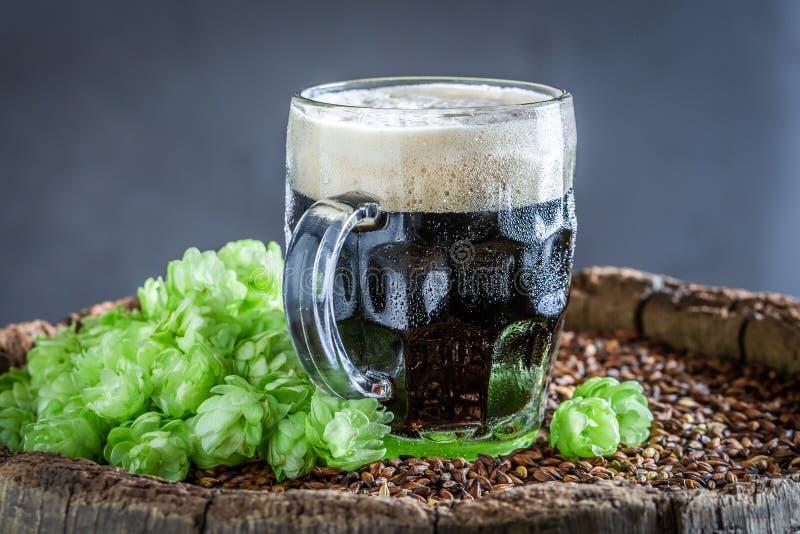 Primo piano di birra scura fredda con schiuma bianca immagine stock