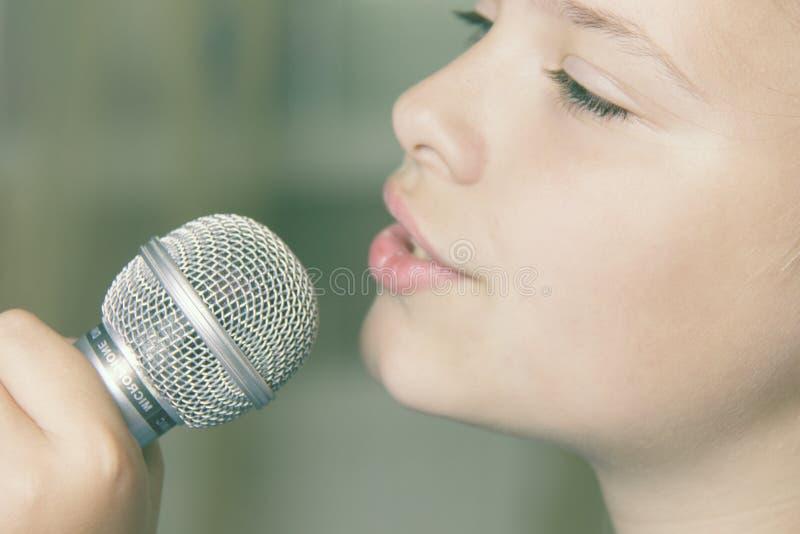Primo piano di canto della ragazza caucasica del bambino La ragazza canta emozionalmente nel microfono, tenente lo con la mano immagini stock libere da diritti