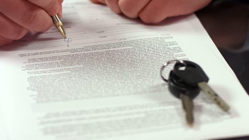 Primo piano di firma di accordo di affitto dell'uomo, chiave dell'automobile sulla tavola, acquisto di trasporto, affare immagini stock libere da diritti