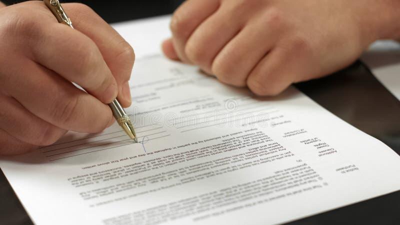 Primo piano di firma del contratto del compratore, approvazione del documento ufficiale, acquisto del bene immobile fotografia stock