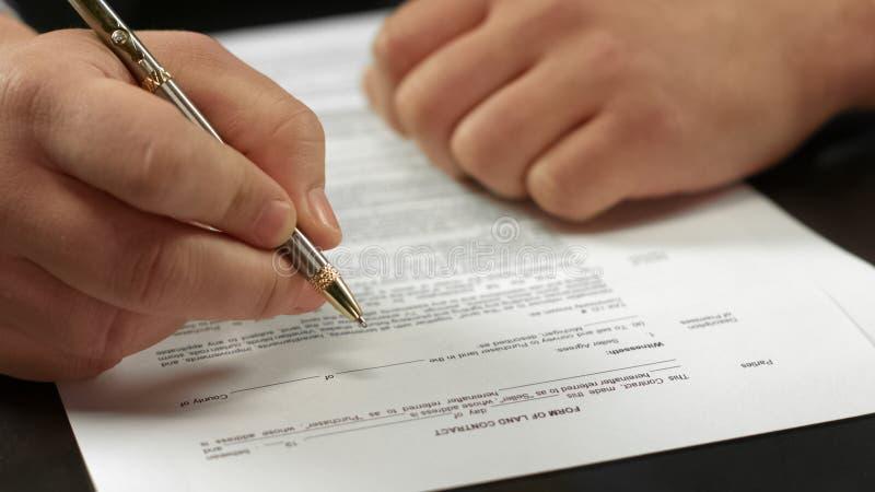 Primo piano di firma del contratto della mano maschio, uomo d'affari che fa affare, approvazione di accordo fotografie stock libere da diritti