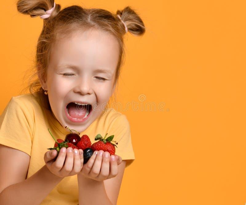 Primo piano di giovane bambino della neonata con una manciata di frutti di bacche in sue mani delle palme che ride grida sul gial immagini stock