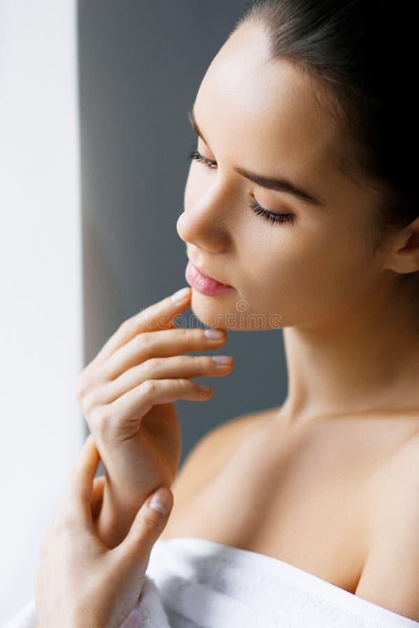 Primo piano di giovane bella donna con trucco nudo che tocca il suo fronte Bellezza, stazione termale Tenuta della lozione d'idra immagini stock libere da diritti
