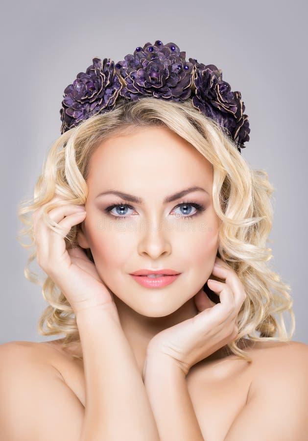 Primo piano di giovane, donna sensuale che indossa la coroncina simile del fiore porpora immagine stock