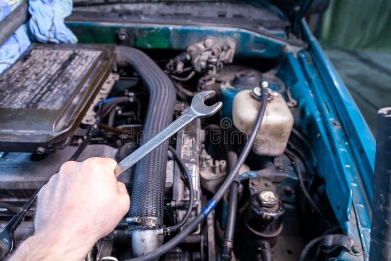 Primo piano di giovane riparatore dell'automobile che tiene una chiave in sua mano immagini stock libere da diritti