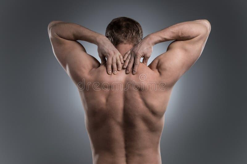 Primo piano di giovane uomo senza camicia con dolore al collo immagine stock
