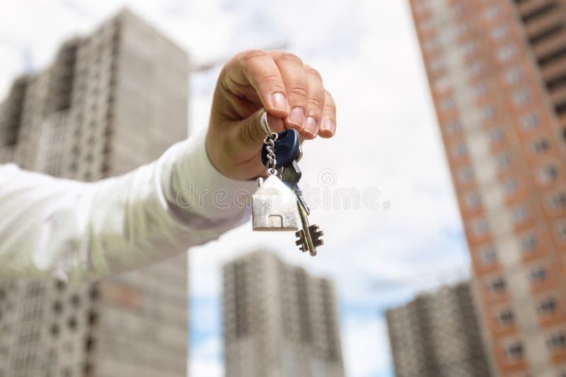 Primo piano di giovani chiavi della tenuta della mano dell'uomo d'affari dalla nuova casa immagini stock