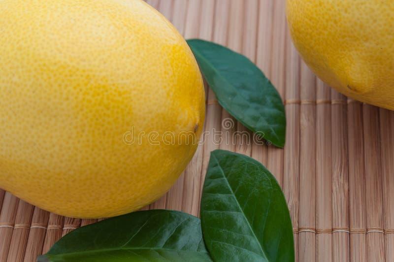 Primo piano di grandi limoni e foglie verdi gialli sulla stuoia di bambù immagine stock