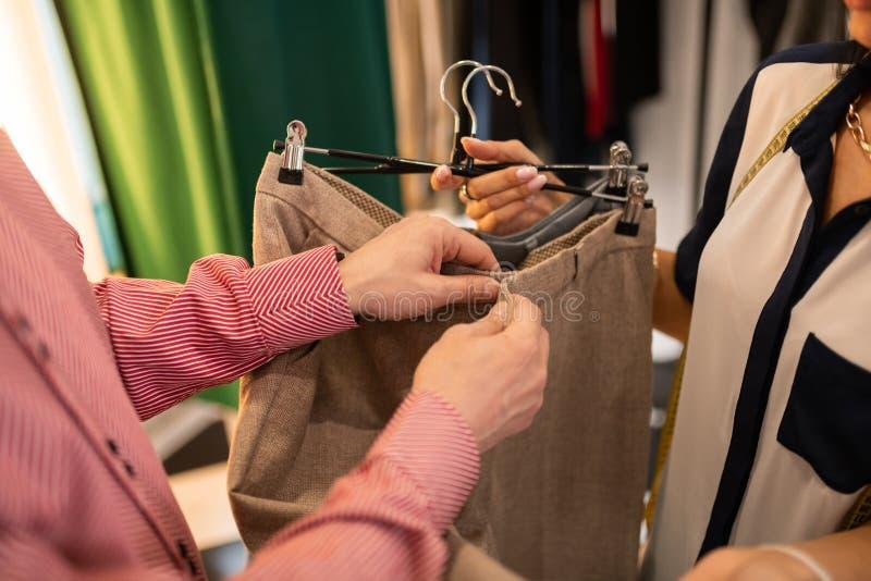 Primo piano di maschio controllando gli accessori dell'indumento dei pantaloni beige immagini stock libere da diritti