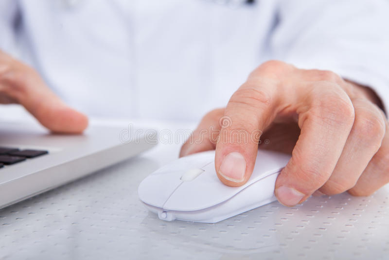 Primo piano di medico che per mezzo del computer portatile fotografie stock libere da diritti