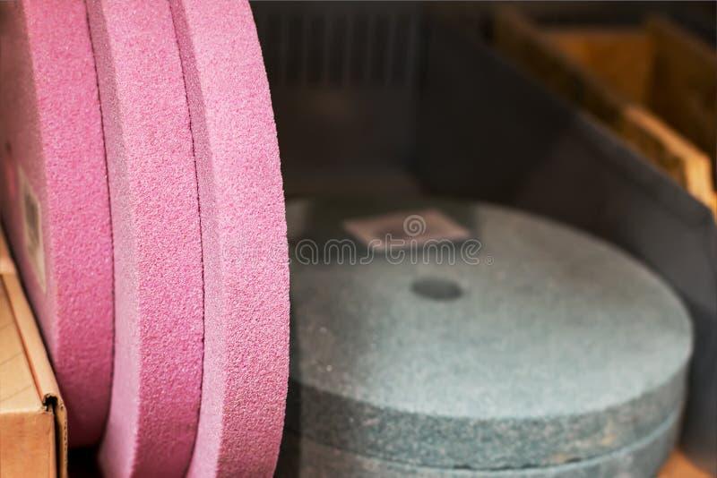 Primo piano di nuove mole del rosa e del colore grigio Nuovo disco abrasivo su uno scaffale in un'officina immagine stock libera da diritti