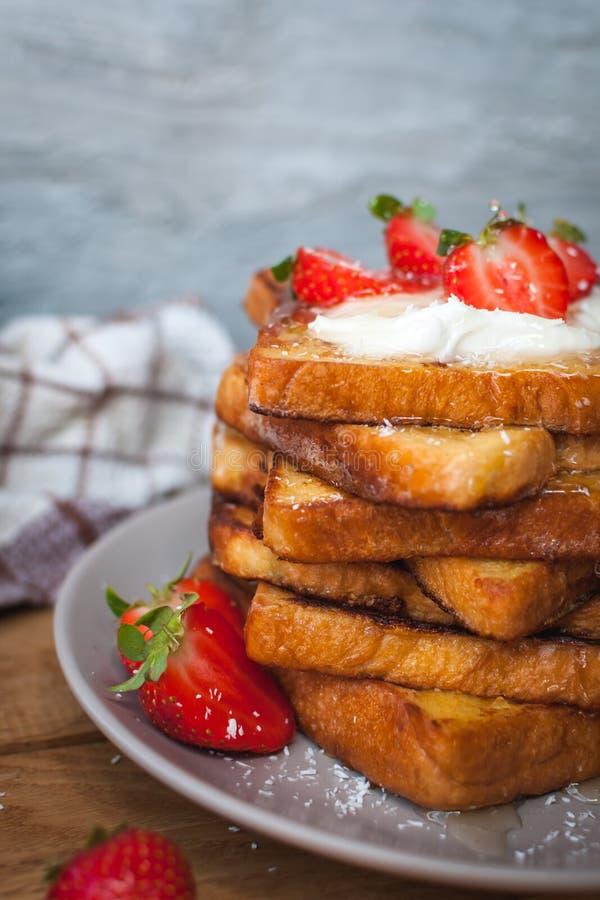 Primo piano di pane tostato francese con le fragole, i brandelli della noce di cocco ed il miele freschi, su fondo di legno immagini stock libere da diritti