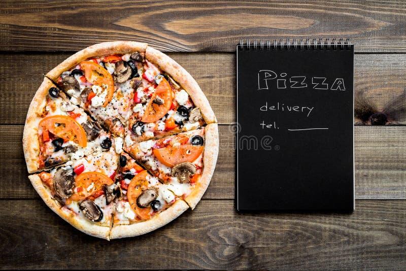 Primo piano di pizza e del taccuino con il testo: Consegna della pizza tavola di legno del fondo Il nero del taccuino con testo b fotografia stock libera da diritti