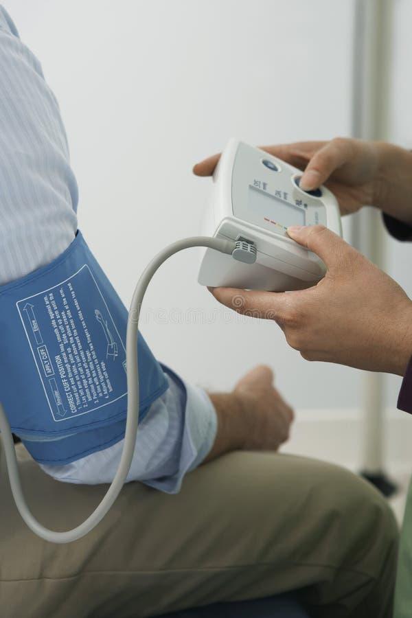 Primo piano di pressione sanguigna del dottore Checking Patient fotografie stock libere da diritti