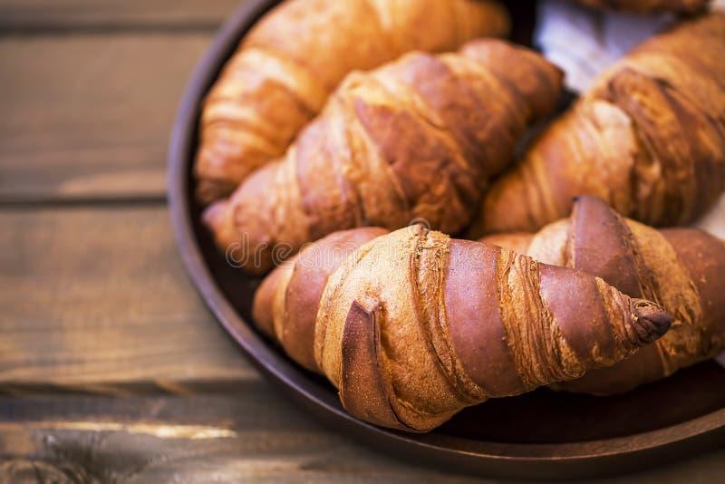 Primo piano di recente al forno dei croissant sulla tavola di legno, croissant francesi freschi, panini della prima colazione immagine stock