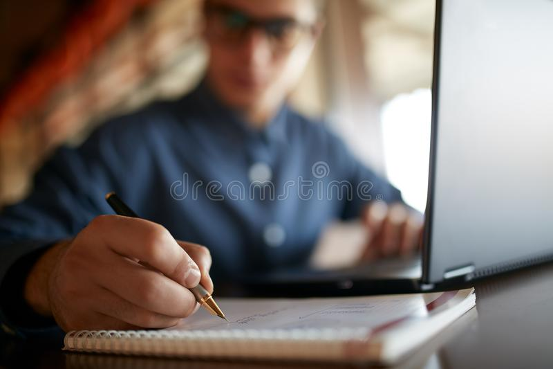Primo piano di scrittura della mano dell'uomo sul taccuino di carta Giovane uomo d'affari in vetri che prendono le note in blocco immagine stock