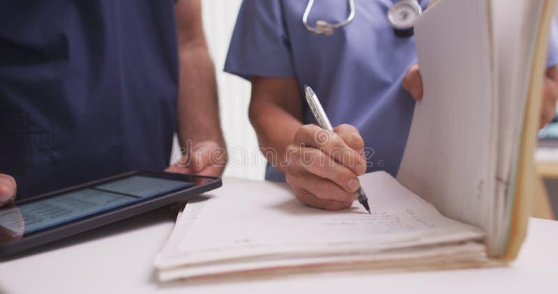 Primo piano di scrittura femminile matura dell'infermiere nella cartella di un paziente fotografia stock libera da diritti