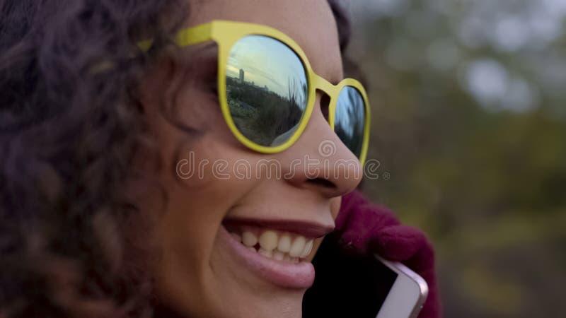 Primo piano di signora felice biraziale in occhiali da sole che discute a fondo telefono, riflessione della città immagine stock libera da diritti