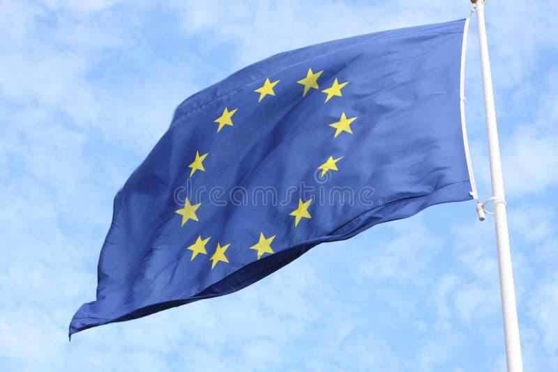 Primo piano di singola bandiera europea con dodici stelle gialle che ondeggiano nel vento davanti a cielo blu illustrazione di stock