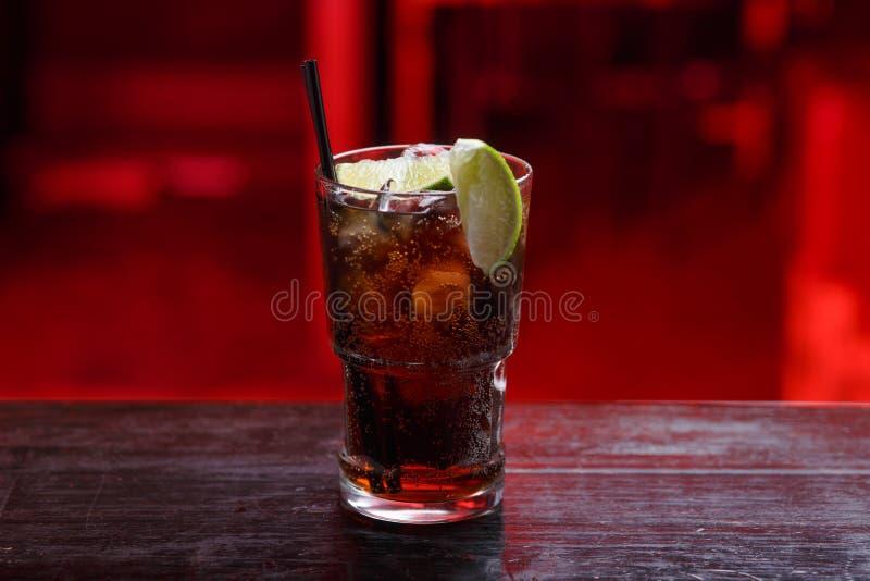 Primo piano di un cocktail di Cuba Libre in breve vetro, gin, stante sul contatore della barra, isolato su un fondo rosso fotografia stock libera da diritti