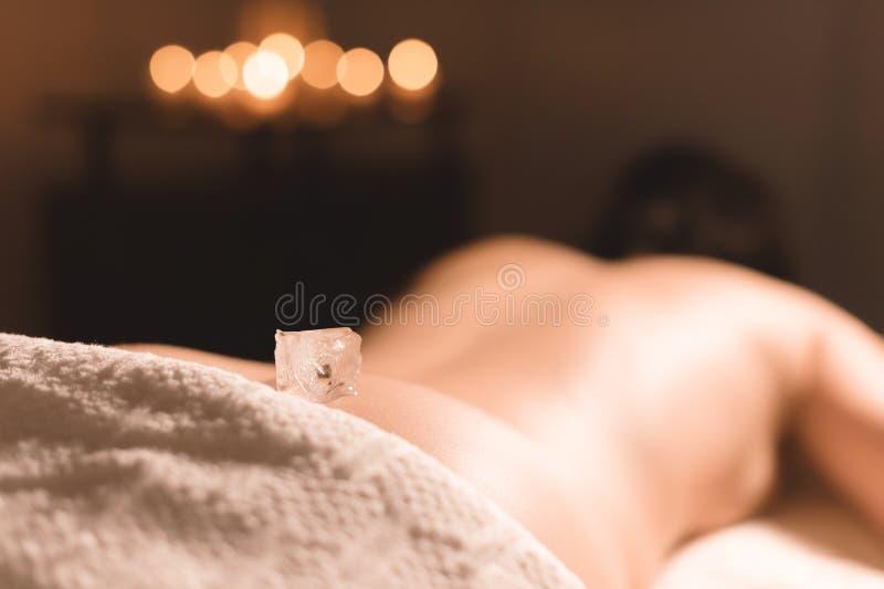 Primo piano di un cubetto di ghiaccio trasparente che si trova sul più lombo-sacrale di una ragazza che si trova su uno strato pe fotografia stock
