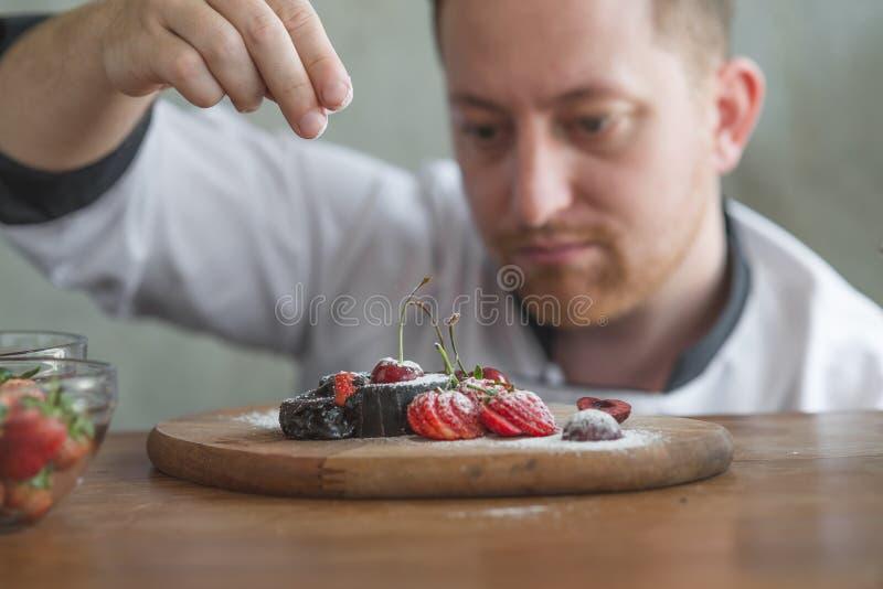 Primo piano di un cuoco unico di pasticceria maschio concentrato fotografie stock libere da diritti