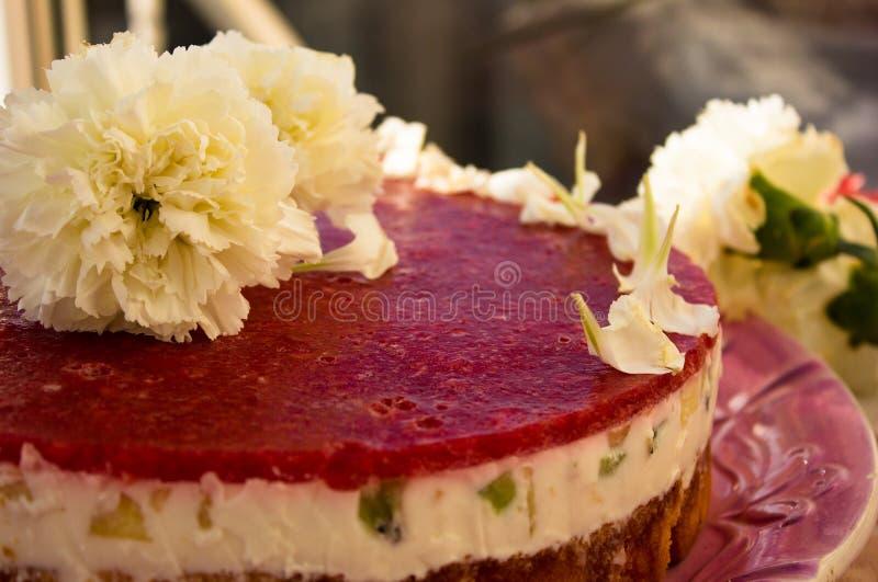 Primo piano di un dolce della fragola dal lato sul pan di Spagna bianco del batskground con gelatina e frutta sui precedenti dell fotografie stock