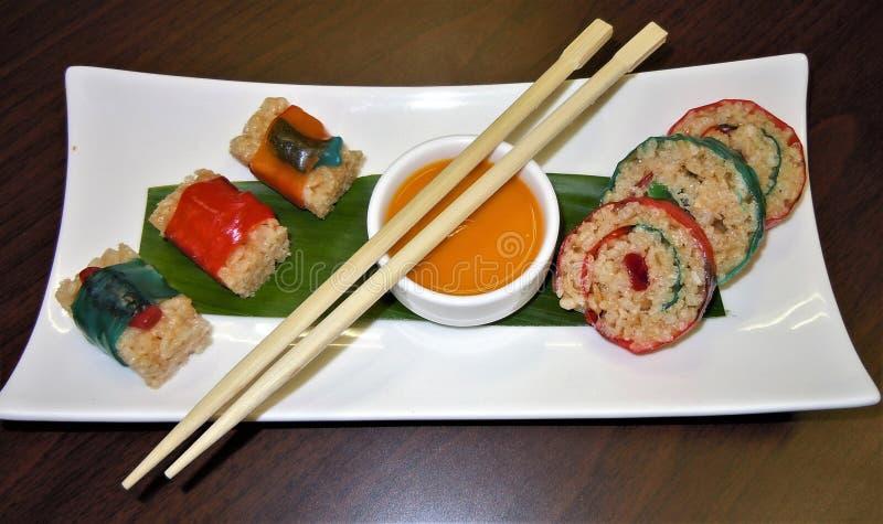 Primo piano di un'esposizione dei sushi, dei bastoncini e della salsa di immersione canditi immagini stock libere da diritti