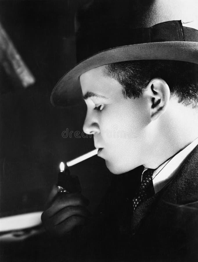 Primo piano di un giovane con un cappello che accende una sigaretta con un accendino (tutte le persone rappresentate non sono viv fotografia stock
