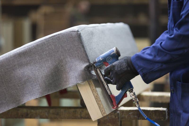 Primo piano di un giovane in una fabbrica della mobilia che un una parte del sofà con una cucitrice meccanica fotografia stock