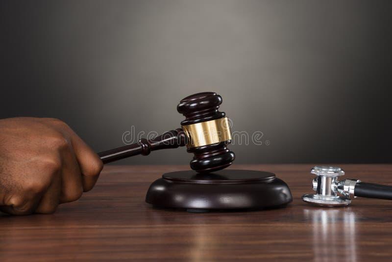 Primo piano di un giudice Hands Striking Gavel allo scrittorio immagine stock