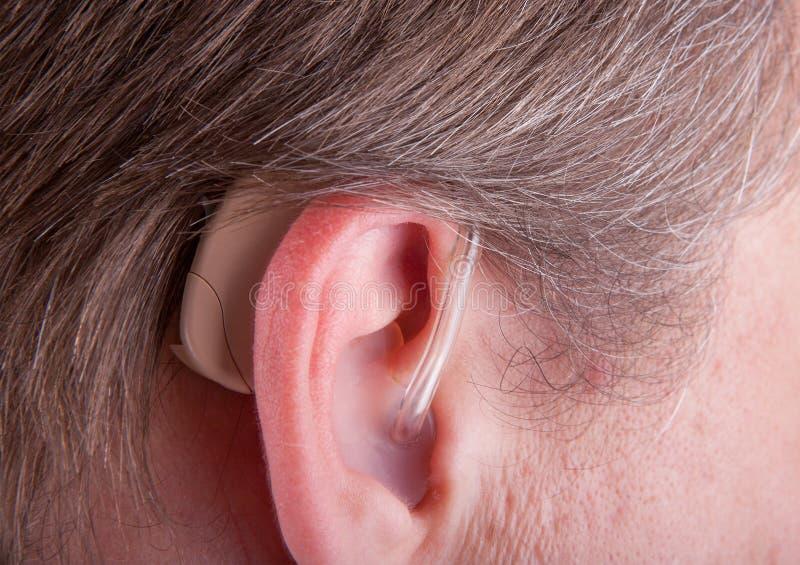 Primo piano di un man& senior x27; protesi acustica d'uso dell'orecchio di s fotografia stock
